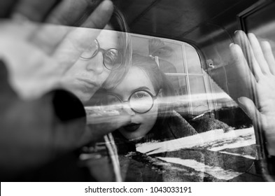 loving couple in glasses and coats, photo through glass, reflections, art house, black and white photo