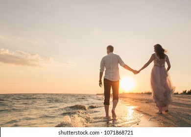 A loving couple going to the sunset on the seashore, she is in a beautiful dress, he is in a shirt, barefoot, happiness. love, future, new relationship, long merry marriage