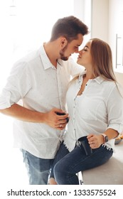 Loving couple have fun at home. Pretty blonde in a white blouse.