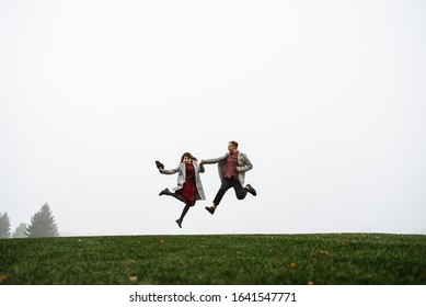 Loving couple have fun together, they jumping on the grass