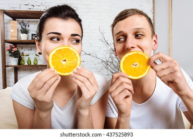 Loving couple having breakfast with fresh oranges