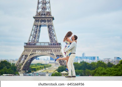 Loving couple having a date near the Eiffel tower. Romantic jump hug. Tourists on vacation or during their honeymoon in Paris, France