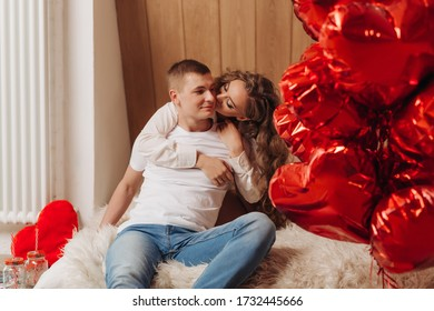 A loving couple is having fun together. Man and woman on a date. guy and girl in the interior of the house on his day off. Lovers hug and feel tenderness for each other