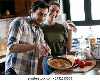 Liebes Ehepaar, das Spaß beim Zubereiten des Essens hat. Freund und Freundin machen Pfannkuchen zu Hause.