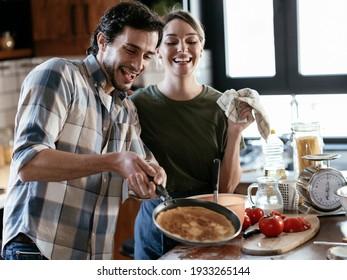 Loving couple having fun while preparing food. Boyfriend and girlfriend making pancakes at home.