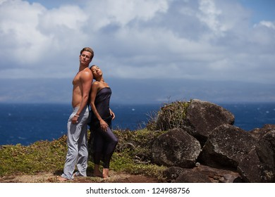 Loving couple in Hawaii above the ocean on a Lava bluff