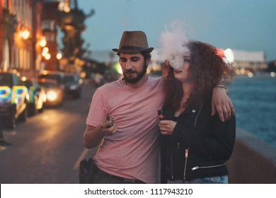 Loving couple of hipsters on date. Guy in hat and T-shirt is holding electronic cigarette and hugging girlfriend. Girl with curly red hair smokes an ecigarette. They are in streets of evening city.