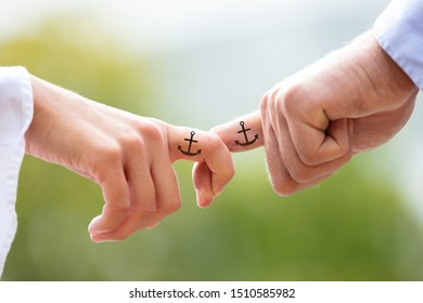 Loving Couple Holding Each Other's Finger With Black Anchor Sign Tattoo Against Blurred Background