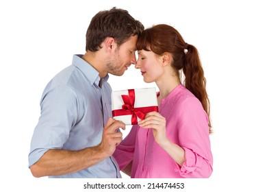 Loving couple holding a gift on white background