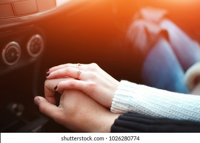 Loving couple holding hands in car. Close up shot of loving couple's hands, man and woman on travel road