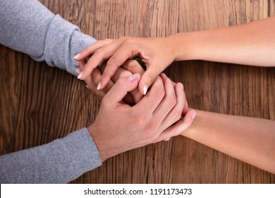 Loving Couple Holding Hands On Wooden Desk