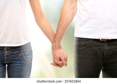 Loving couple holding hands on sunny nature background
