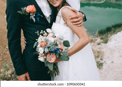 Loving couple holding hands with rings and bouquet against wedding dress