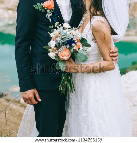 Loving couple holding hands with rings and bouquet against wedding dress and lake