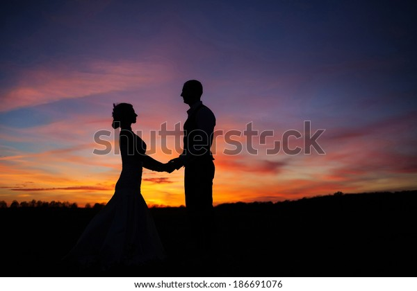 loving couple holding hands at sunset