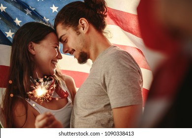 Loving couple holding sparklers wrapped under American flag. American man and woman celebrating independence day.