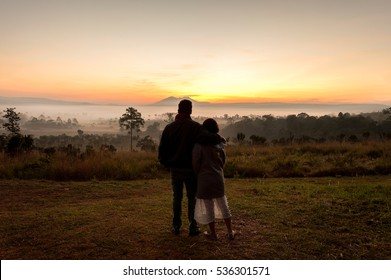 Loving couple hug one another during romantic date to camera, looking at Savanna field in the mist with mountain background.