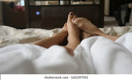 Loving couple hug and play their feet each other under blanket while wake up in bed in the morning