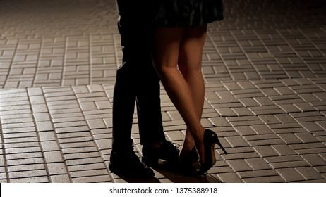 Loving couple hugging and kissing in the street, view of legs, relationship