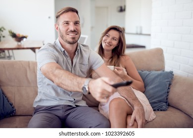 Loving couple hugging and smiling. They watch TV and the man switches channels.