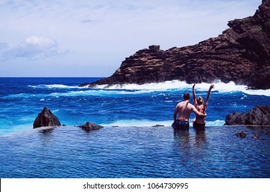 Loving couple hugs at the edge of a natural swimming pool of lava, watching the ocean in city of Porto Moniz. Madeira Portugal