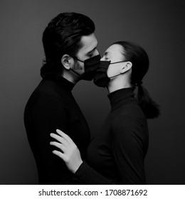 Loving couple kisses in medical masks
