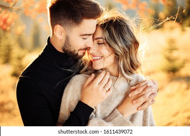 Loving couple kisses in the mountains near a tree in autumn