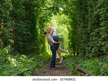 Loving couple kissing in a green tunnel