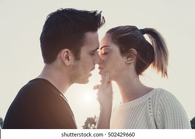 Loving couple kissing outdoor at sunset - Concept about people, love and lifestyle