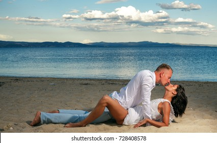 Loving couple kissing outdoor at sunset. Concept about people, love and lifestyle. Just one kiss. Fashion man and white shirt. Couple in love. Jeans dress. Sexy photo. Sensual. Sea background. Sexy