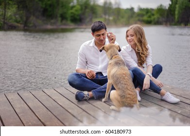 Loving couple at the lake, with dog, a love story