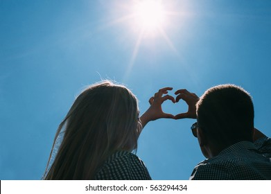 Loving couple looking at the blue sky and the sun with outstretched hands making a shape of heart. Man and woman blondes