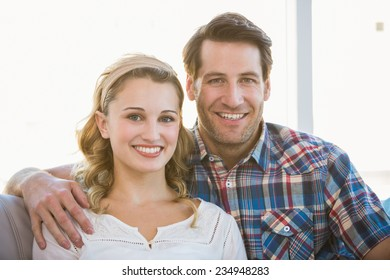 Loving couple looking at the camera in bright living room