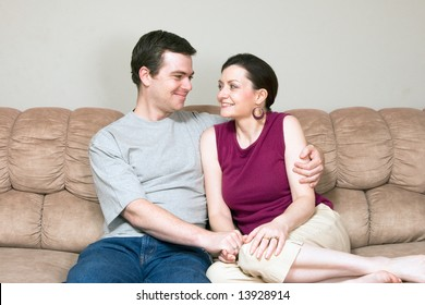 A loving couple looking at each other smiling and sitting on a sofa.  The man has his arm around the woman.