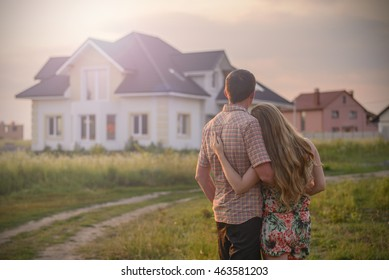 loving couple looking at their home in sunset. Copy space