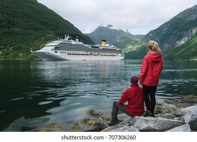Loving couple looks dreamily at a cruise ship in the fjord. Geirangerfjord near the town of Geiranger, Norway