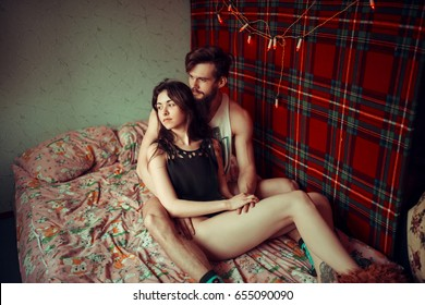 Loving couple lying in bed together. Handsome young hipster with beard and attractive woman resting at home while kissing and cuddling