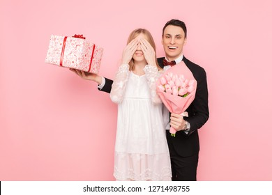 A loving couple, a man gives a shocked woman a bouquet of tulips and a box with a gift on a pink background. Valentine's Day Concept