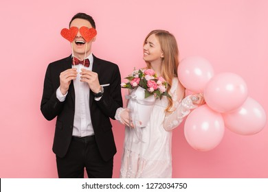 A loving couple, a man holds two paper hearts in his eyes, and a woman holding a bouquet of flowers and balloons in the studio on a pink background