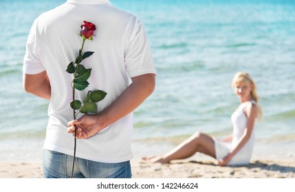 loving couple - man with rose waiting his woman on the sea beach at summer - the romantic date or wedding or valentines day concept