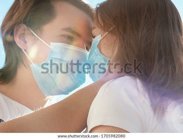 Loving couple with medical face masks looking at each other.
