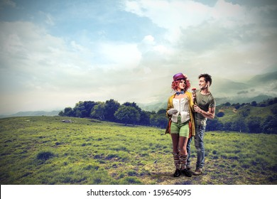 loving couple in the middle of a meadow in the mountains