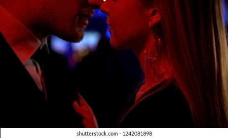 Loving couple moving to music at night club close to each other, romantic date