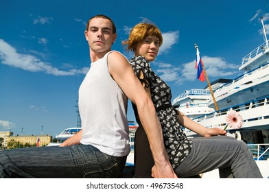 Loving couple near the cruise liners. Teenagers: girl and fellow are in harbor