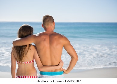 Loving couple on the beach embracing one another while looking at the sea