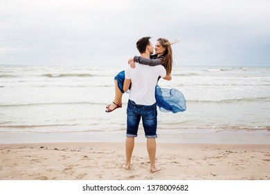 Loving couple on the beach. Man holding a woman in his hands.