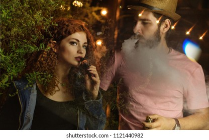 Loving couple on date. Guy and girlfriend smoke electronic cigarettes. Red-haired girl. Man in the hat and t-shirt.
