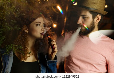 Loving couple on date. Guy and a friend smoke electronic cigarettes and look into each other's eyes. Red-haired girl. Man in hat and t-shirt. Lights of night city shine.
