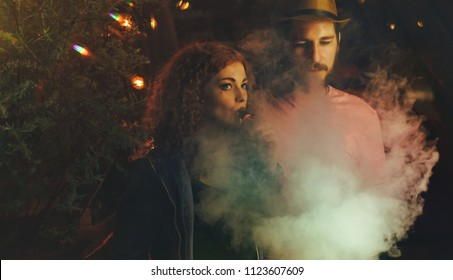 Loving couple on date. Guy and girlfriend smoke electronic cigarettes. Clouds of smoke. Red-haired girl. Man in hat and t-shirt. Lights of night city shine.