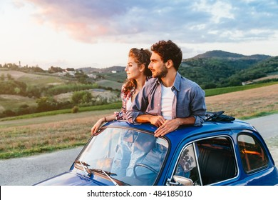 Loving couple on summer afternoon watching sunset from roof by old car around classical landscape of Tuscany, vineyards and farmland